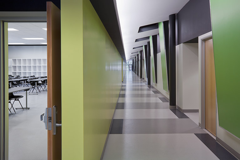 An image of a small empty classroom hallway with a green, gray and white color combination.