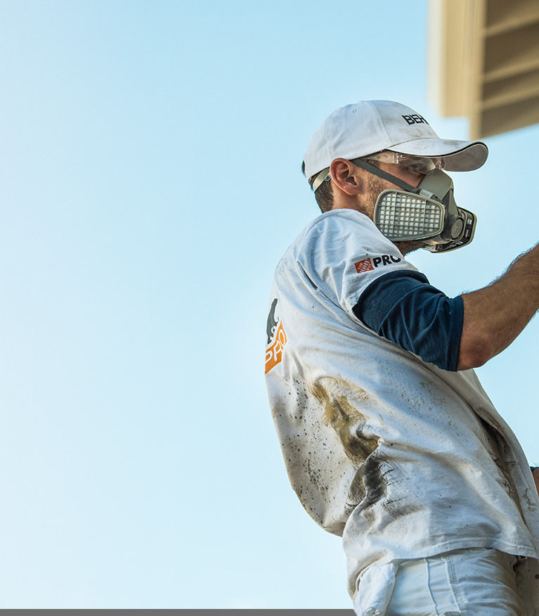 Mobile view of an Image of a Pro Contractor wearing a hat and shirt with Behr logo spray painting an exterior wall of a house on a ladder.