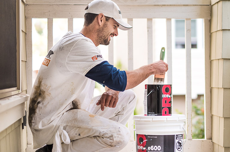 A mobile view of a Pro Contractor wearing a cap and shirt with Behr logo dipping a paint brush on a 1 gallon of BEHR PRO e600 paint can on a porch that he is going to paint.