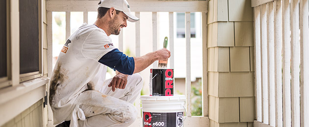 Pro Contractor wearing a cap and shirt with Behr logo dipping a paint brush on a 1 gallon of BEHR PRO e600 paint can on a porch that he is going to paint.
