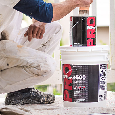 A close up shot of a BEHR PRO e600 1 gallon stacked on top of a 5 gallon. The body image of a contractor next to the can image shows him dipping paint brush on the 1 gallon paint can.