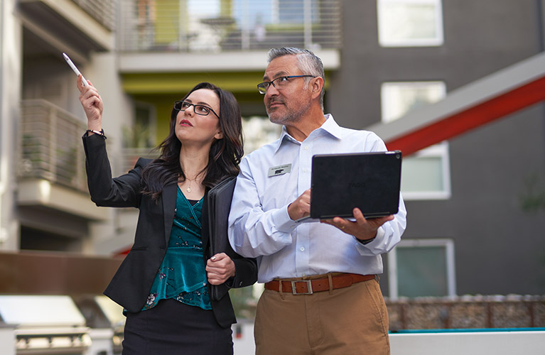 A small image of a Property Manager showing a BEHR PRO Rep a multi-family complex. The property manager is pointing at something while the BEHR PRO Rep is looking at what she is pointing and taking notes on a laptop.