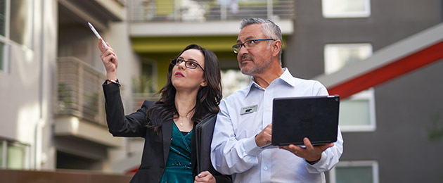 A Large Image of a Property Manager showing a BEHR PRO Rep a multi-family complex. The property manager is pointing at something while the BEHR PRO Rep is looking at what she is pointing and taking notes on a laptop.