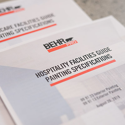 Close up images of a BEHR PRO document for Hospitality Facilities Guide Painting Specification on a table.