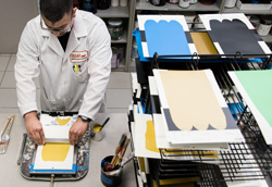A BEHR employee in a lab coat matching several drawdown colors.