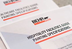 A BEHR PRO Hospitality Guide Painting Specifications and Healthcare Facilities Guide Painting Specifications documents on a terrazzo surface.