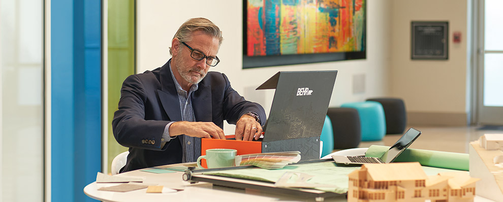 A small image of an architect seated looking at some colors from the BEHR Architectural Color Box