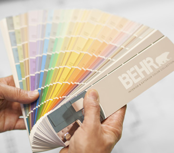 A BEHR Color Fan Deck held by a hand.