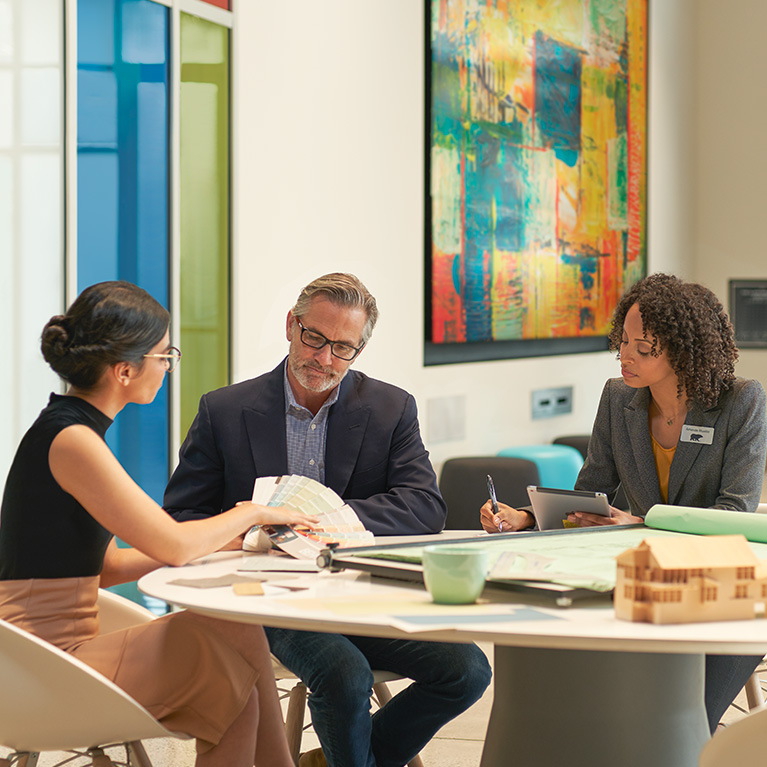 Small image of 3 seated architects in an meeting room discussuing colors and looking at a BEHR Fan Deck