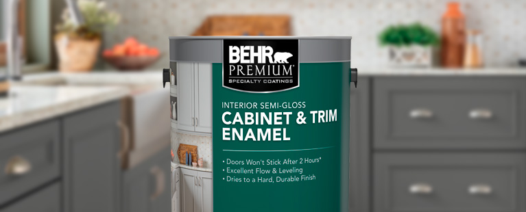 Image of a 1 gallon can shot of BEHR PREMIUM Cabinet & Trim. The background is of a kitchen cabinet and is blurred.