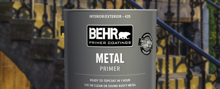 Close up view of a 1 gallon Behr  Metal Primer with the image of a metal staircase railing in the background.