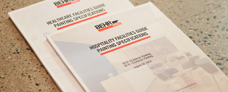 Close up image of a BEHR PRO Hospitality Guide Painting Specifications and Healthcare Facilities Guide Painting Specifications documents on a terrazzo surface.
