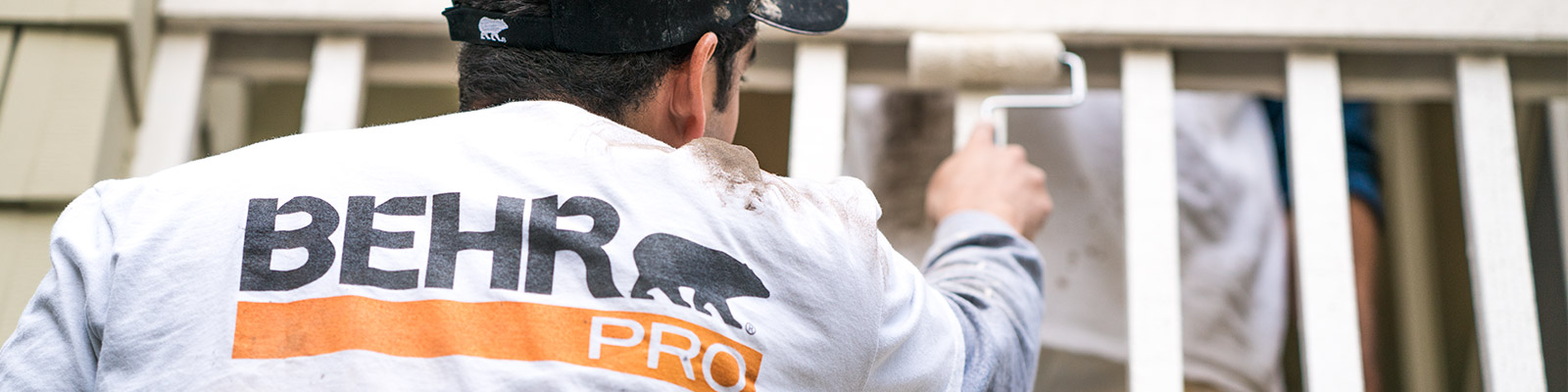 A close-up image of a back of a painting contractor who is painting with a roller with the logo of BEHR PRO imprinted on the shirt..