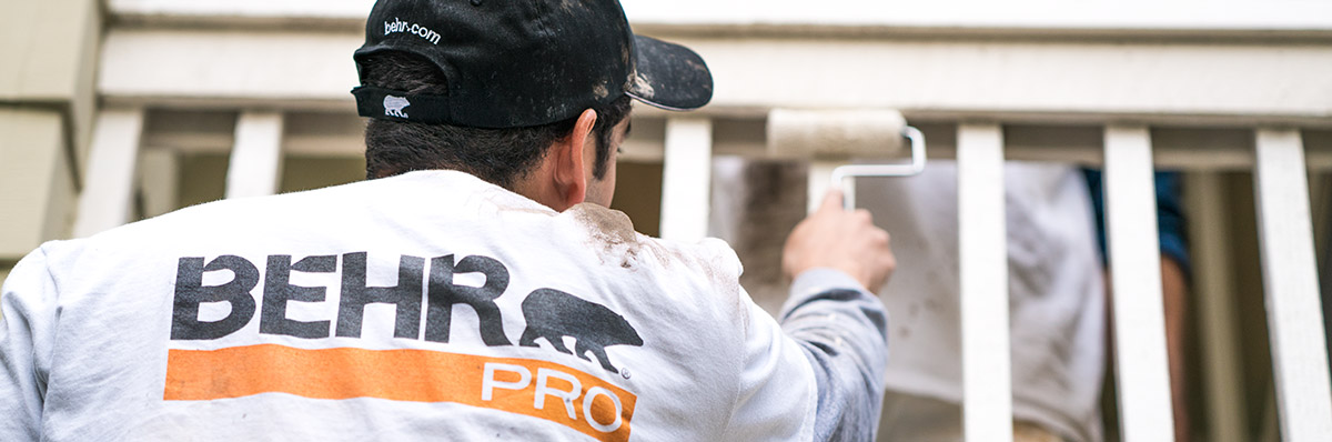 Large close up image of a back of a painting contractor who is painting with a roller with the logo of BEHR PRO imprinted on the shirt.