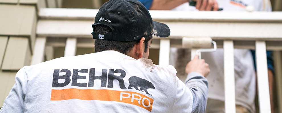 Small A close up image of a back of a painting contractor who is painting with a roller with the logo of BEHR PRO imprinted on the shirt.