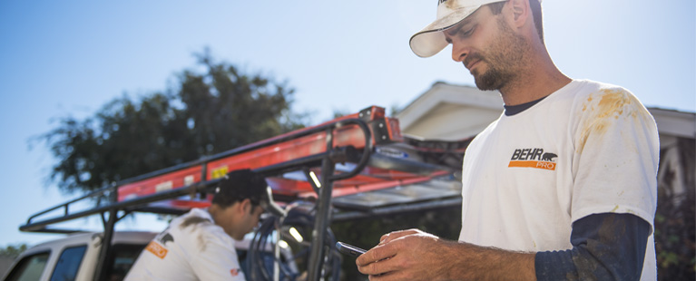 Painting contractor with a BEHR PRO shirt checking his mobile phone
