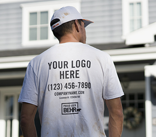 Desktop view of  Pro facing a house. The back of his shirt is on focus with the words in-printed Your Logo here - Fake Telephone # - companyname.com and a logo of PROUD USER BEHR.