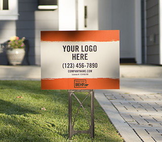 A close up view of a yard sign that is displayed on a front lawn. The Yard sign is printed with the words YOUR LOGO HERE - (123) 456-7890 - company.com - PROUD USER BEHR.