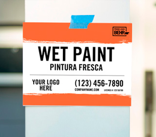 A close up view of a sign that is stuck to a column of a house with the words printed WET PAINT - PINTURA FRESCA - your logo here- (123) 456-7890 - companyname.com - PROUD USER BEHR
