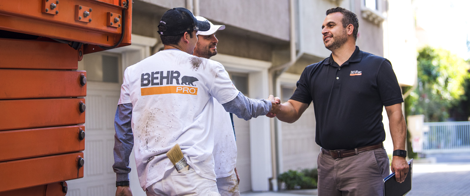 A BEHR PRO Rep shaking hands with on of the 2 Pro Painters. In the background is a multi family condo units.