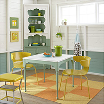 Dining room with green table and 2 yellow chairs and a yellow highchair