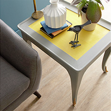 Dark gray chair next to gray and yellow table