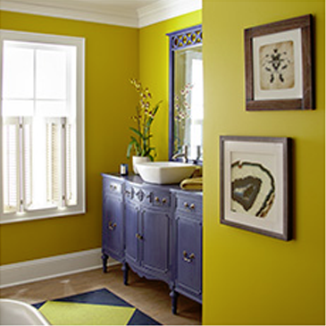 Yellow room with blue dresser, window, and two pictures hanging on the wall