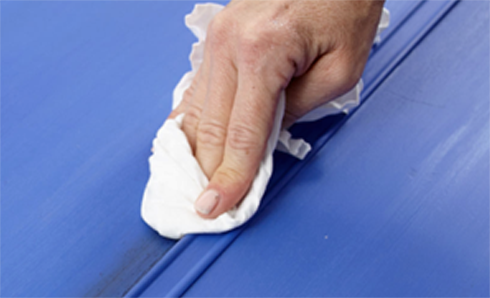 Person's hand using a rag wiping a blue wall