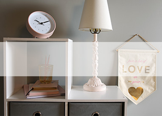 Shelf with clock and lamp on it with a small banner hanging on the wall that says love