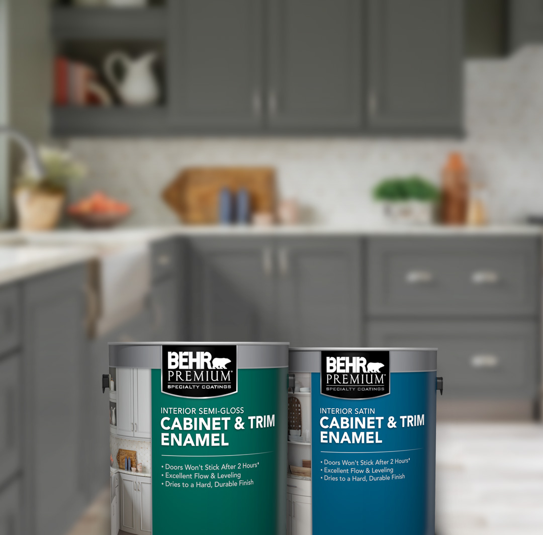 Mobile version of 2 cans of Behr Cabinet & Trim Enamel Pant in front of kitchen cabinets.