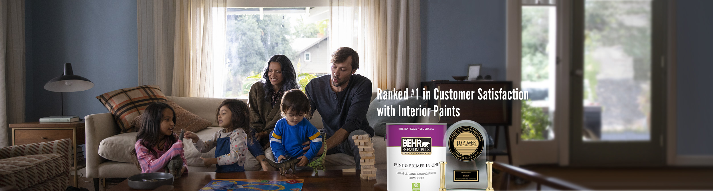 Can of Behr paint and award with family in the living room in the background
