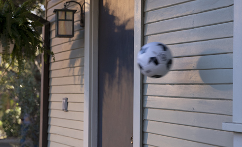 Soccer ball being bounced off the siding of a house