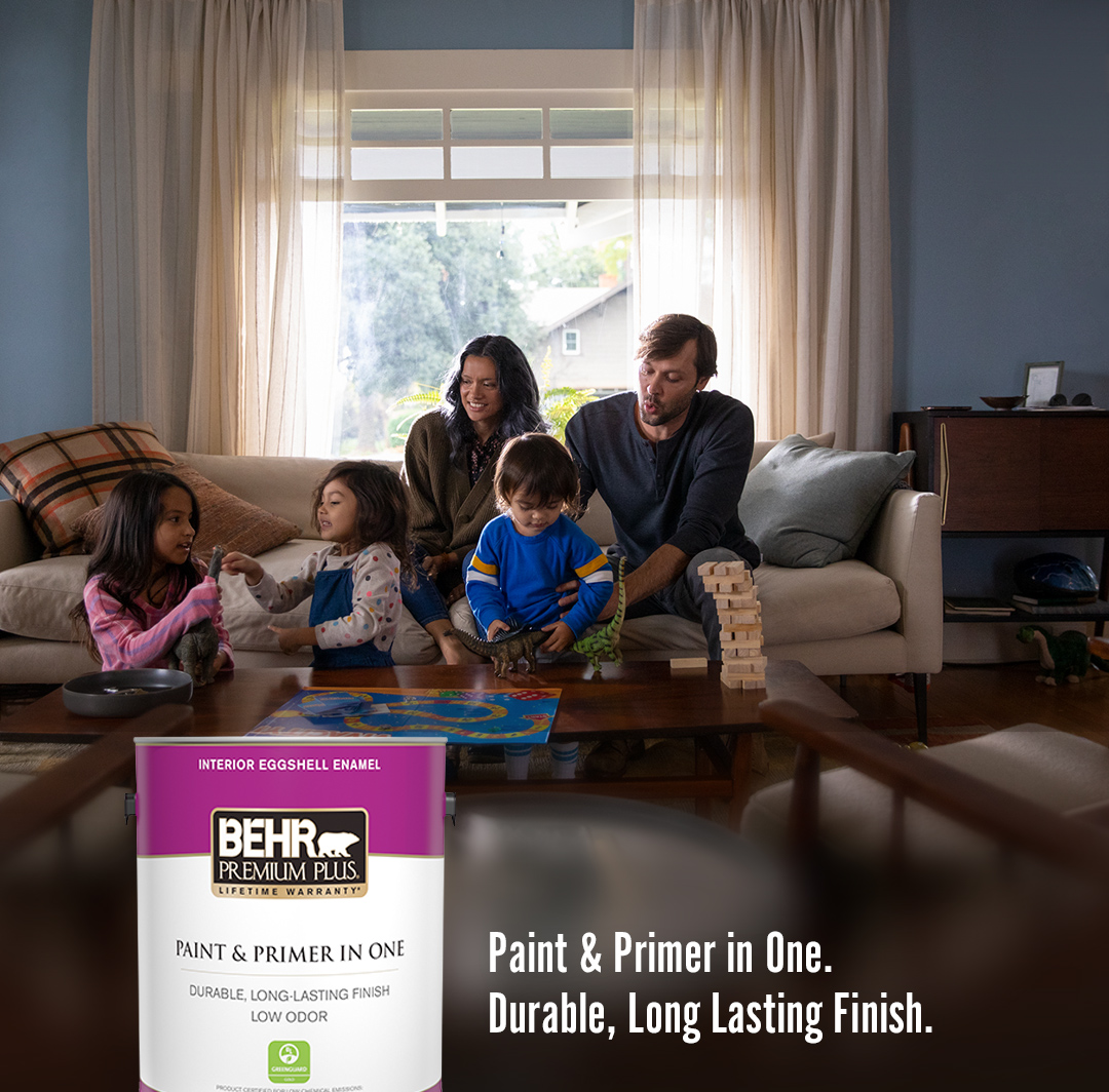 Mobile sized image of family of 5 sitting on living room sofa with a can of Premium Plus Interior Eggshell Enamel in foreground.