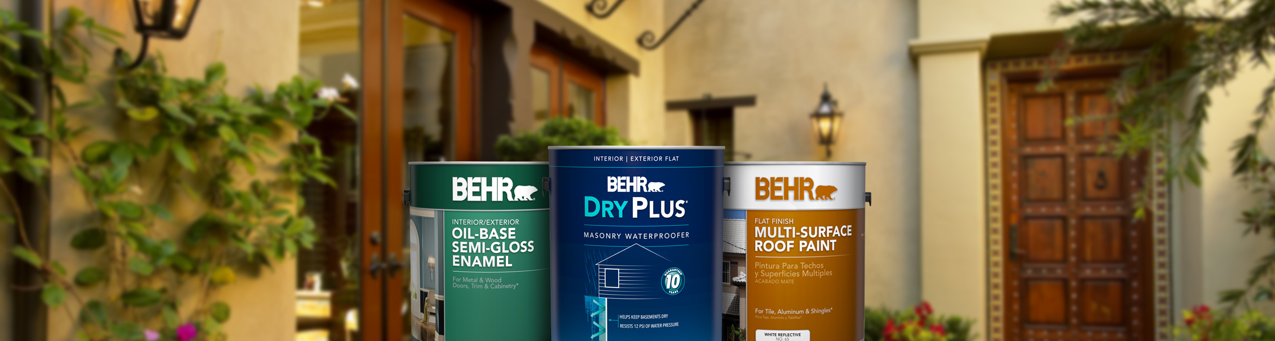 Three cans of Behr paint and front side view of home with greenery in the background