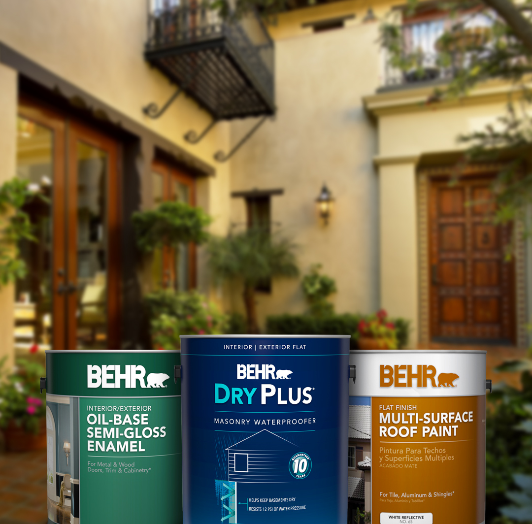 Three cans of Behr paint with large home and greenery in the background