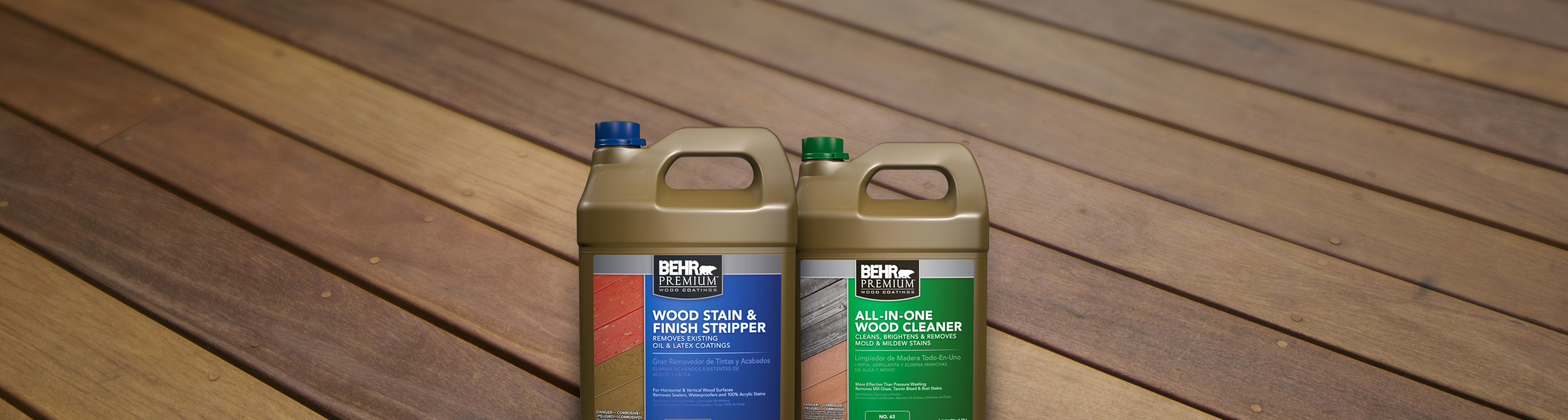 Two bottles of Behr wood stain cleaner with deck in the background