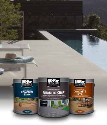 Three cans of Behr Premium Paint with pool in the background