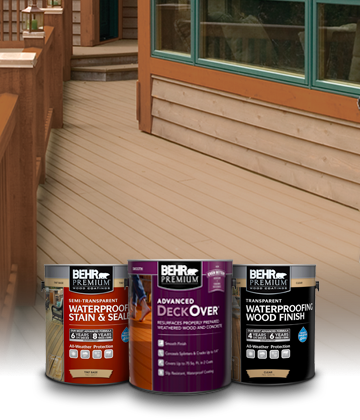 Three cans of Behr Premium Deck Paints and Stains sitting on a tan deck