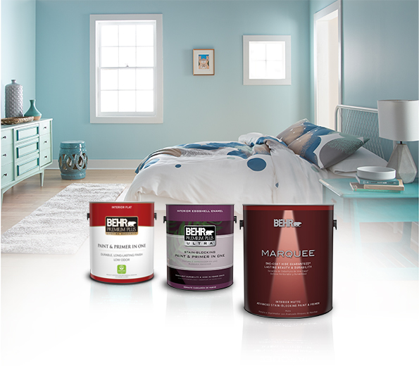Three cans of Behr Paint with blue bedroom and bed in the background