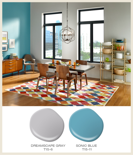 A modern-eclectic dining room featuring colors rug under dining table and blue accent wall.