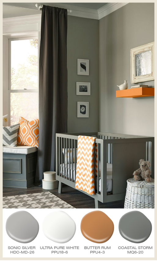 A gray tone-on-tone baby nursery with pop of mango color accents.