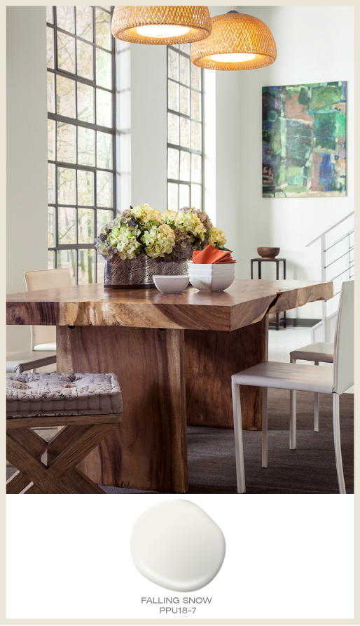 A modern loft dining area featuring natural toned dining table and seating stool.