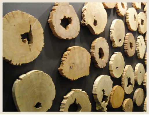 A wall art installation featuring many medallion-like wood log slices.