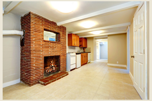 A basement with a kitchen and red brick fireplace.