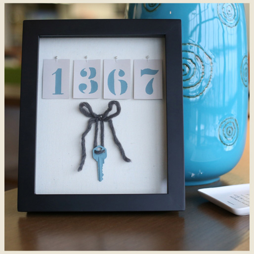 A painted house number and key display in a black frame.