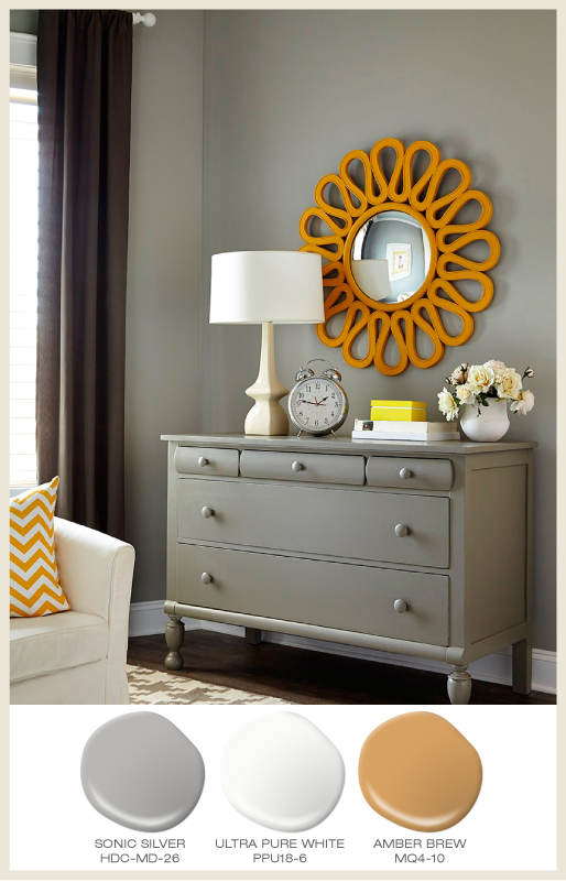 A tone on tone nursery room with dresser and an amber gold color mirror frame.