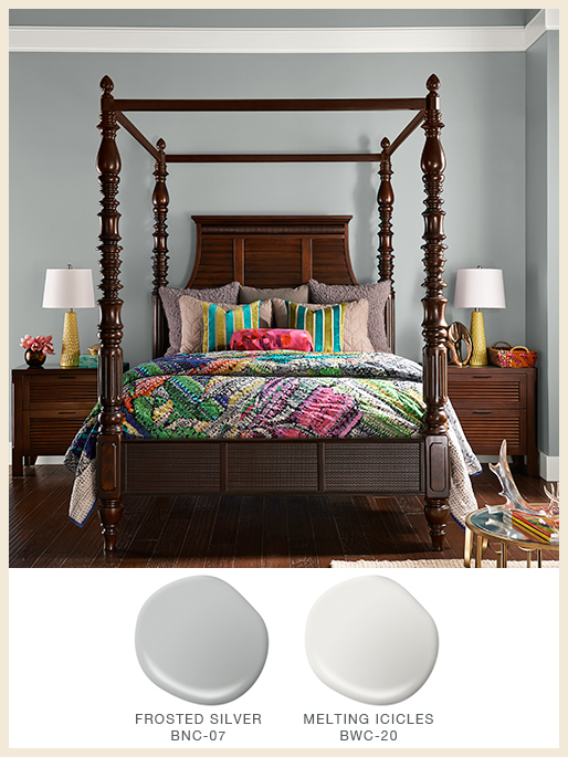 A global style bedroom with light gray walls and dark wood furniture.