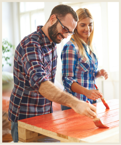 A woman and man painting a wood furniture piece with a bright red color.