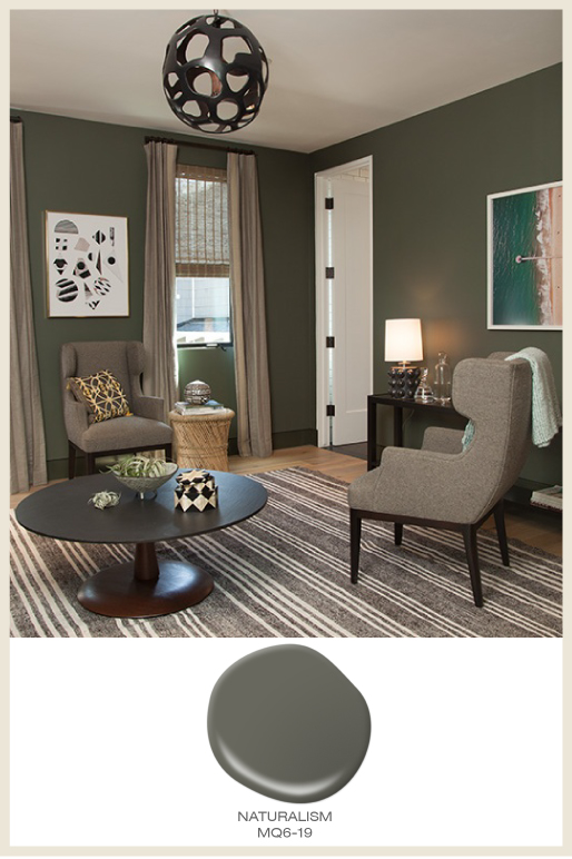 A cozy sitting area with walls painted in a dark olive green color called Naturalism.