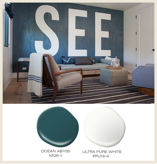 A living room with an accent wall painted in dark blue textured paint and over-sized textwith the word SEE.